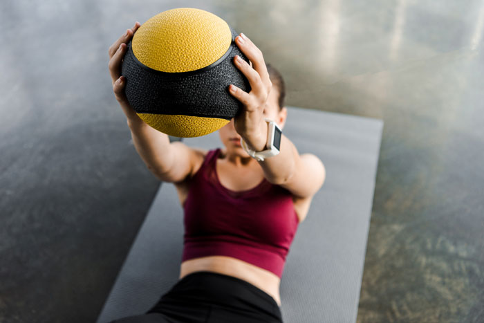 woman doing exercise with medicine ball